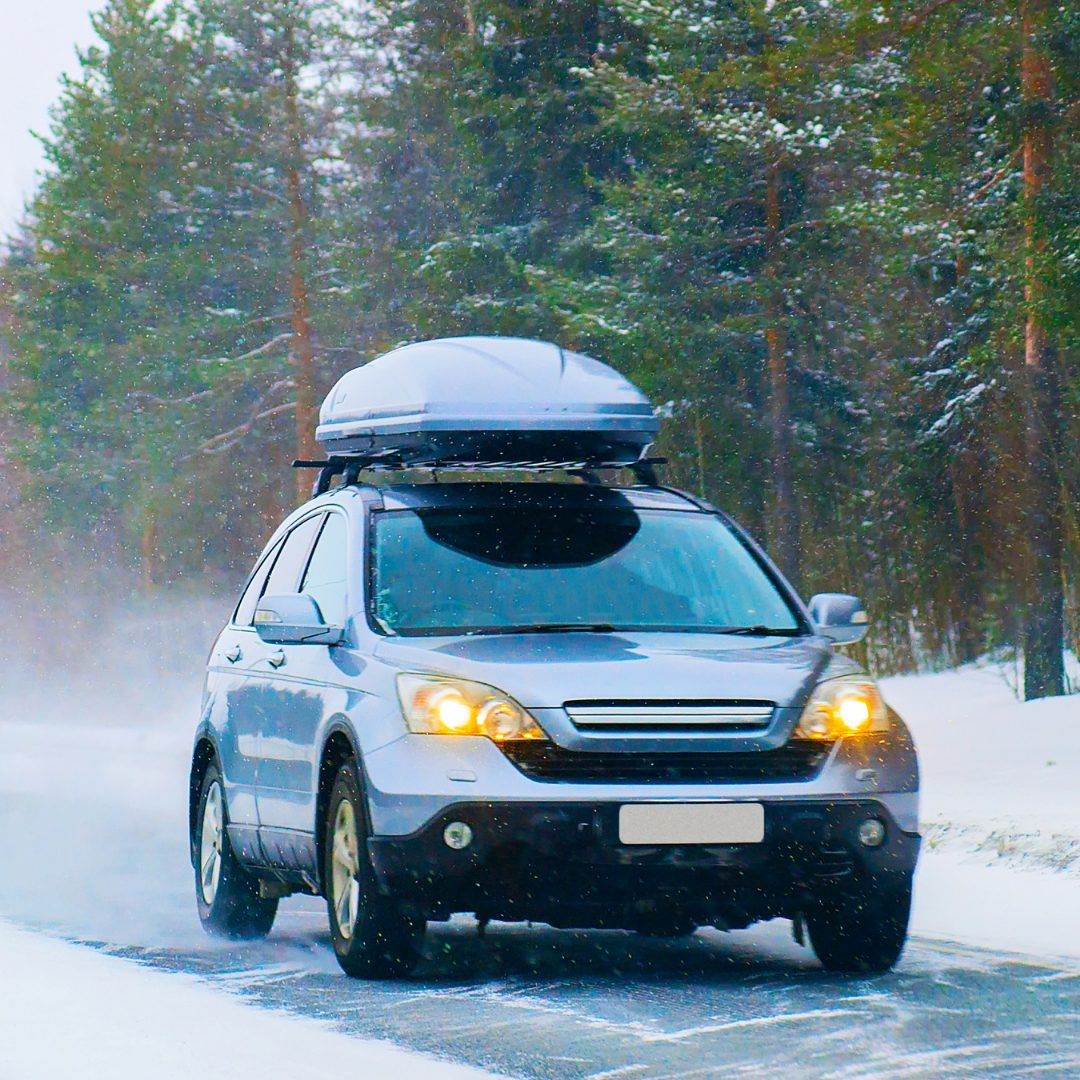 car driving on a snowy road with a roof box